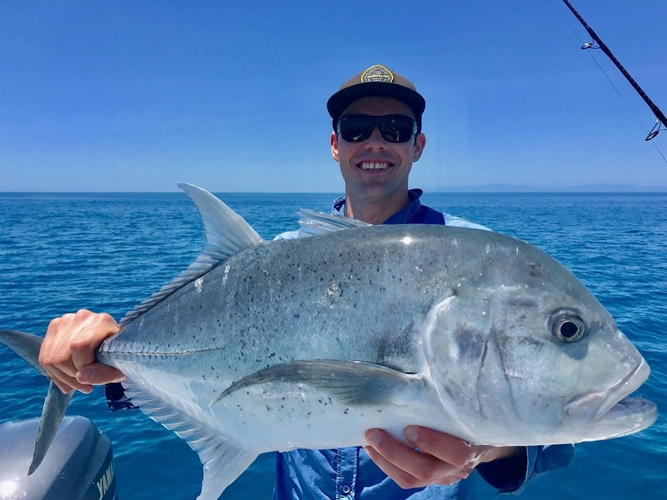 Game fisherman showing a trevally fish with blue skies and calm waters