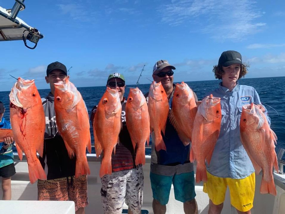 group of male anglers showing their red emperor catch