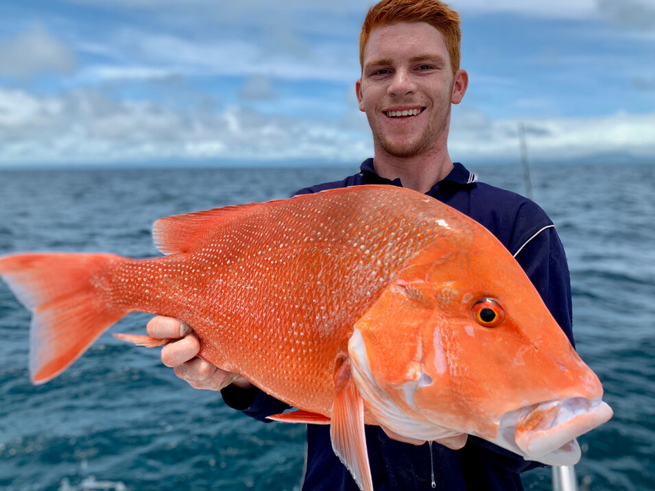 Man with reddish hair holding a nannygai fish