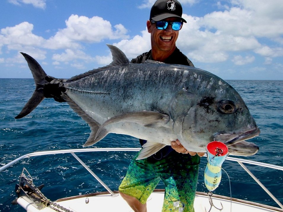 An angler with cap presenting his giant trevally at popper reef fishing