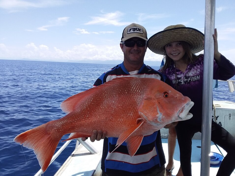 male and young female angler holding a red emperor