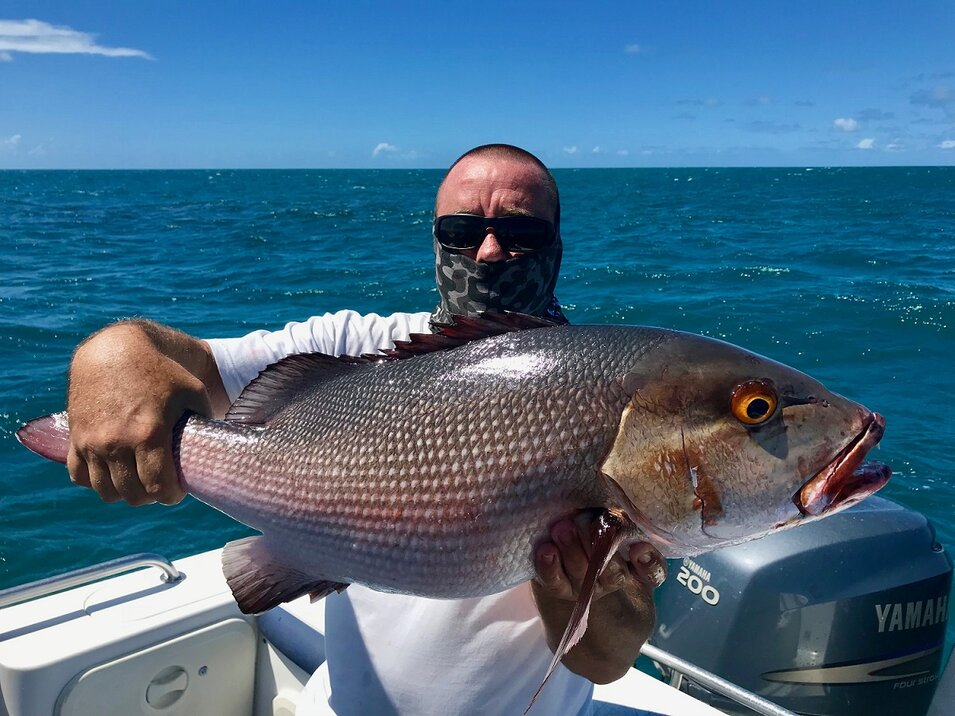 male angler holding a great barrier reef fish