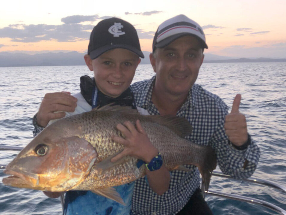 Father and a son holding their fingermark fish catch